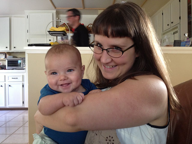 A picture of me with a smiling baby Julia in a blue oneside
