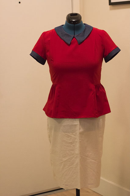 Dressform with a white muslin skirt and red blouse