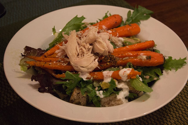 A white bowl filled with salad greens, roasted carrots, and other vegetables, drizzled with yogurt dressing.