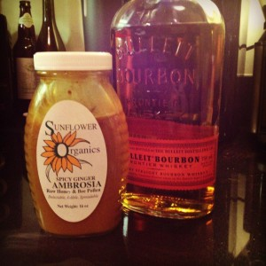 A bottle of bourbon and a bottle of honey sitting on a counter.