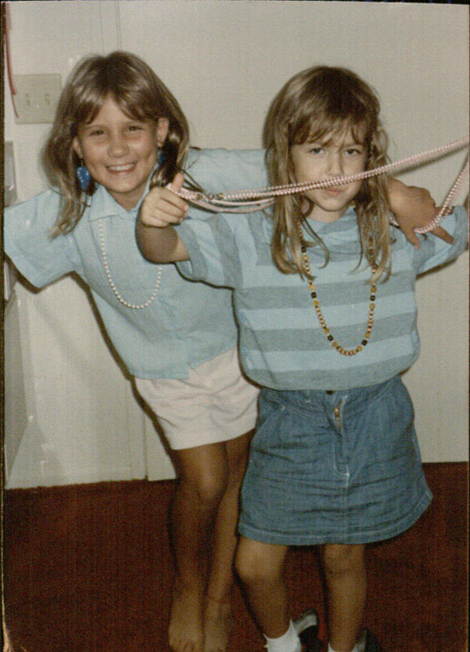 Two young girls in the 1980s, playing dress up.