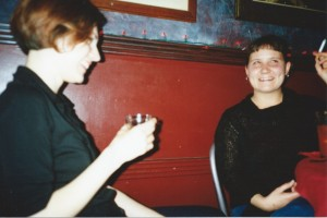 Two girls in a bar, wearing black, laughing