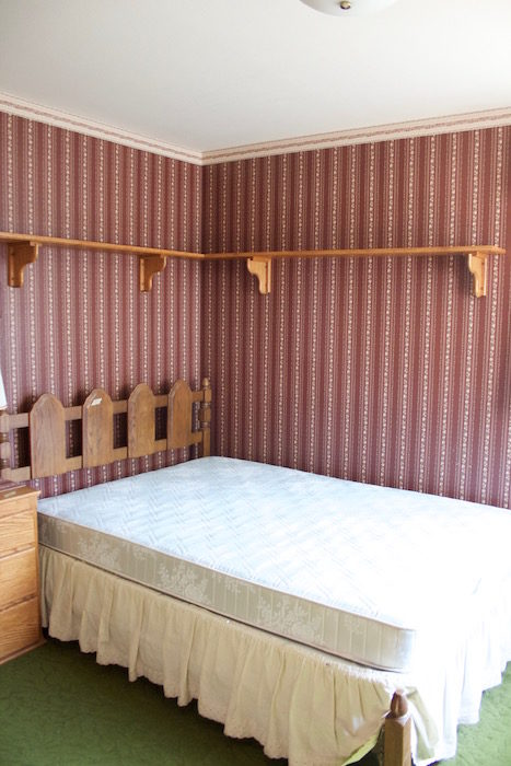 A bed with bare mattress and bed skirt in a purple wall papered room.