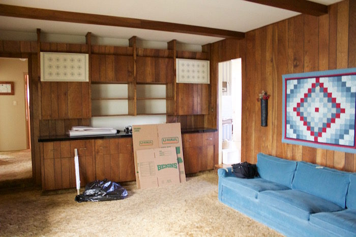 A wood paneled room with a blue couch, a quilted wall hanging, and some moving boxes and trash bags.