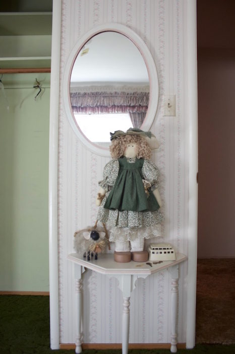 A two-foot tall Little Bo Peep doll with sheep on a demi-lune table, under a mirror.