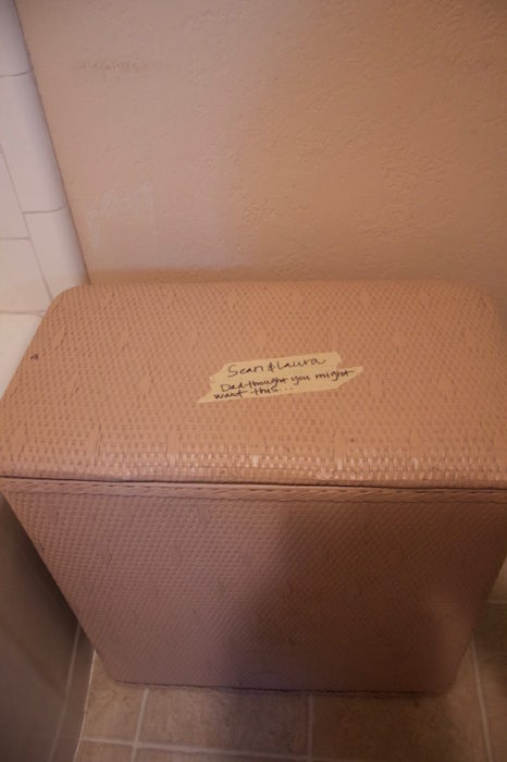 """A pink wicker hamper with a masking tape label that says """"Dad thought you might want this."""""""