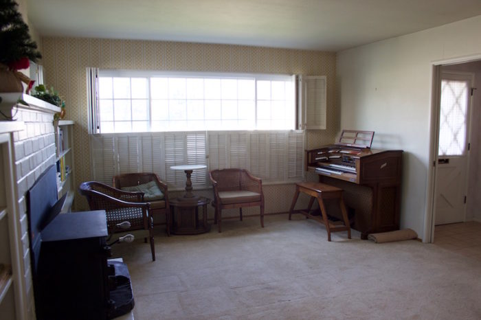 A living room with chairs, end tables, books, and a 1970s-era organ.