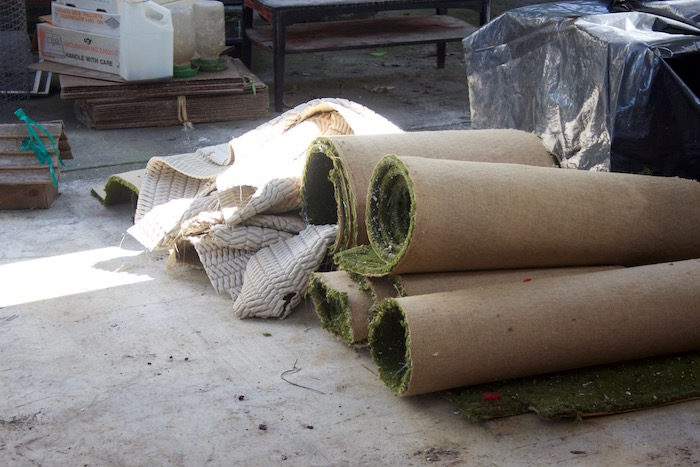 Rolls of green carpet and a small pile of dirty, white carpet pad piled up outside on a concrete pad, surrounded by other debris.