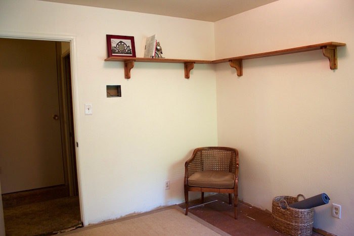 Mostly empty room with a wooden shelf on the wall, wicker and wood chair, sisal rug, and basket with a yoga mat in it.
