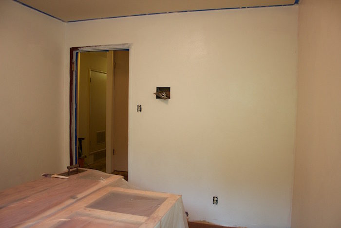 A nearly empty room with painters tape marking the ceiling, light plates and wall fixtures removed, painted white.